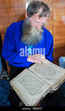 Old believer, the Russian community of old believers reads an antique Bible. - Stock Image