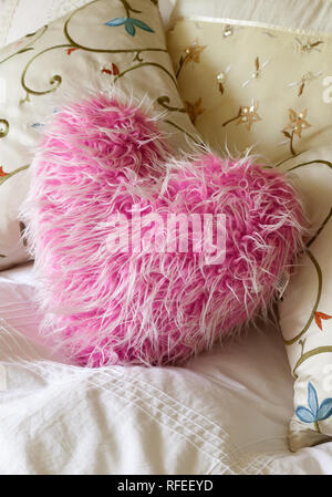 fluffy soft pink heart shaped cushion on bed. - Stock Image