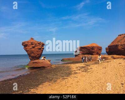 Tourists at the tea cup rock on Prince Edward Island Canada - Stock Image