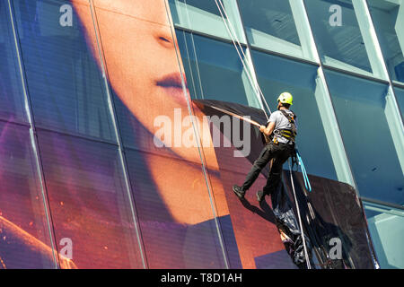CANNES, FRANCE - APRIL 2019: Specialist maintenance operative abseiling down the side of the Palais des Festivals in Cannes to remove plastic advertis - Stock Image