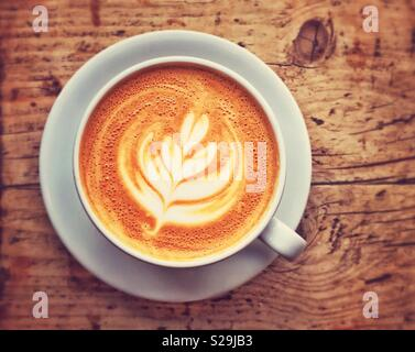 An overhead view of a cup of Latte coffee. An interesting outline shape of white milk predominates. You can't beat a rustic wooden table for a background! Photo Credit - © COLIN HOSKINS. - Stock Image