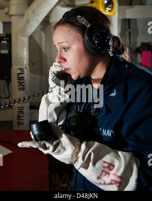 A Sailor relays messages during a fire drill at sea. - Stock Image