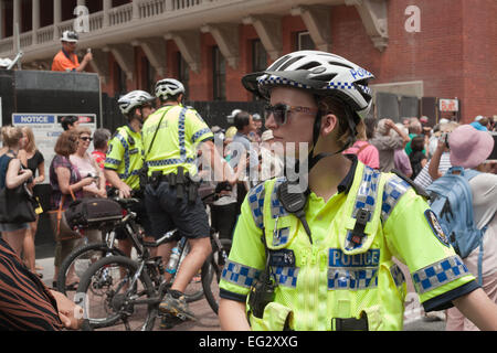 Female Western Australia police bicycle officer with two male colleagues in the background - Stock Image