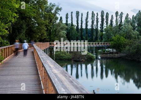 Wooden bridge above water with people walking - Stock Image