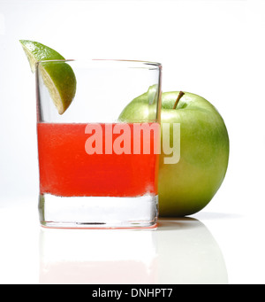 A colorful cocktail drink in a glass with a wedge of lime and a whole green apple. - Stock Image