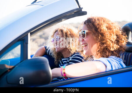 Couple of curly cheerful woman smiling and having fun together enjoying the travel vacation driving the car - people on the move in convertible vehicl - Stock Image
