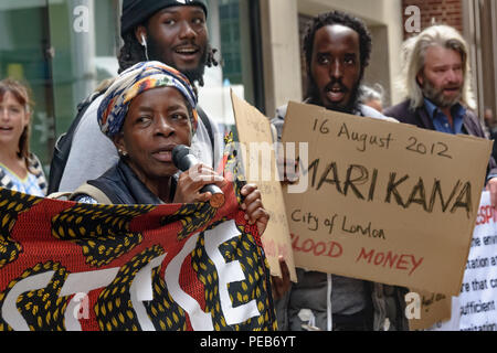 London, UK. 13th August 2018. Protesters outside the Majedie offices. Three days before the 6th anniversary of the massacre when 34 striking miners were shot dead by South African police at Lonmin's Marikana platinum mine, a tour of the City of London visited investors, insurers and shareholders profiting from the violence against people and nature in Marikana and heard about the colonial roots of the huge wealth of the City. Credit: Peter Marshall/Alamy Live News - Stock Image