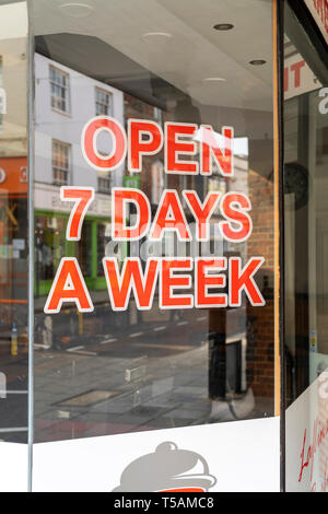 Open 7 days a week sign in shop window - Stock Image