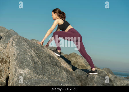 cross country fitness., woman bouldering over rocks - Stock Image