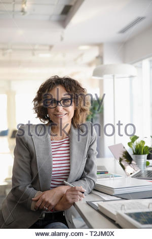 Portrait confident businesswoman working in office - Stock Image