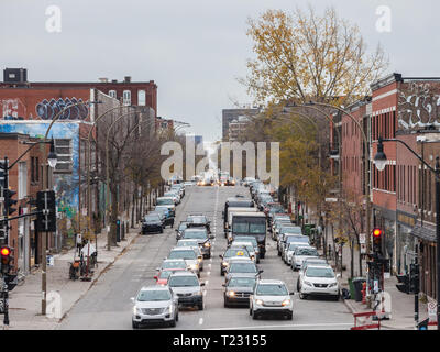 MONTREAL, CANADA - NOVEMBER 9, 2018: Typical Shopping street in Le Plateau district, with small and medium businesses, and cars passing by in a traffi - Stock Image