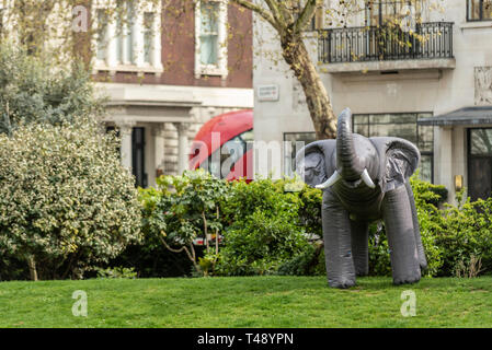 Inflatable elephant at a stop trophy hunting and ivory trade protest rally, London, UK. Isolated in Cavendish Square park - Stock Image