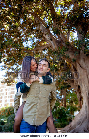 Boyfriend plays with his girlfriend carrying her up her back in a public park in an European city - Stock Image