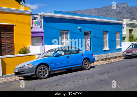 Blue car parked in front of blue house in Bo Kaap, With table Mountain in back. Cape Town, South Africa, March 21, 2019. - Stock Image