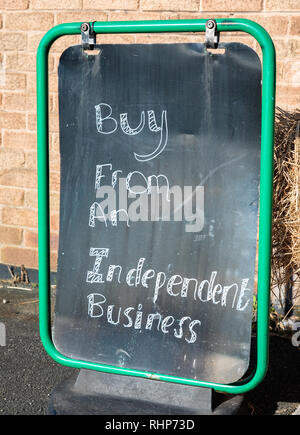 close up of a metal sign with a black background and white lettering outside a local shop encouraging people to buy from an independent business Walla - Stock Image