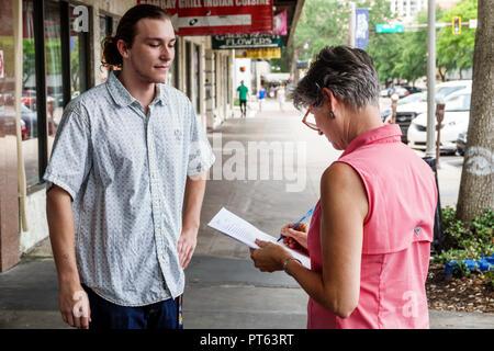 St. Saint Petersburg Florida Central Avenue survey questionnaire opinion poll woman man asking questions street sidewalk - Stock Image