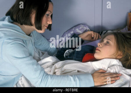 teenage girl consoling her friend who is lying on the bed with a hangover or high on substance abuse - Stock Image