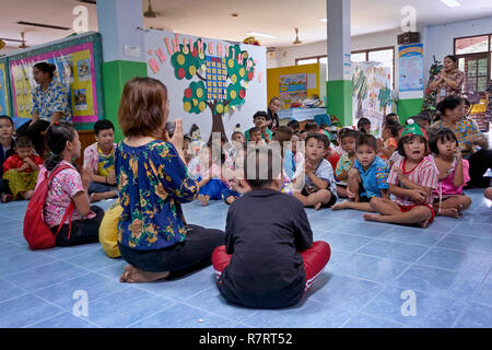 Thailand school. Teacher praying with young children in a Thai school classroom - Stock Image