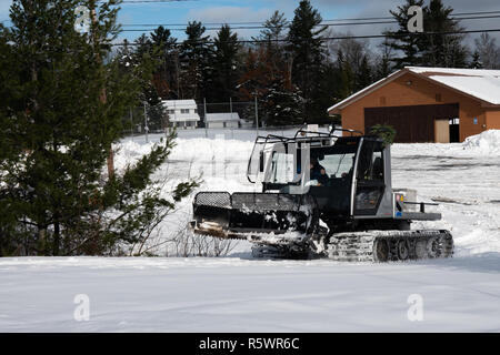 A Prinoth  Husky snow groomer plowing a snowmobile trail in Speculator, NY USA - Stock Image