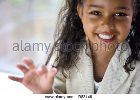 pretty young black girl aged 4 5 smiling and looking excited and waving - Stock Image