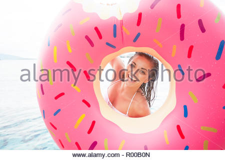 Young woman looking through inflatable donut - Stock Image