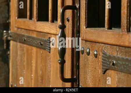 A shot of a handle on an old wooden door - Stock Image