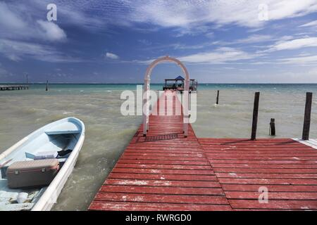 Wooden Boat Dock Pier and tropical Caribbean Sea on Caye Caulker Island, famous winter travel destination in Latin American country Belize - Stock Image