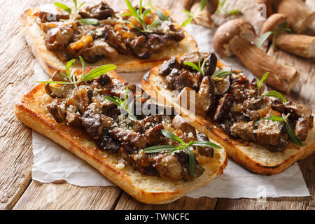 Italian homemade sandwiches with fried boletus mushrooms, onions, thyme and parmesan cheese closeup on the table. horizontal - Stock Image
