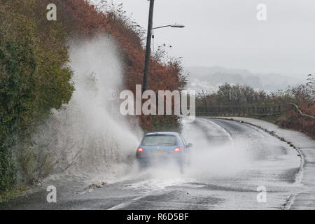 Car driving through a large puddle in the road spraying up water - Stock Image