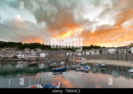 "Mousehole, Cornwall, UK. 20th June 2019. UK Weather. On the eve of the midsummers solstice, rain clouds give a brief shower over the harbour town of Mousehole, once described by Dylan Thomas as the 'best village in England"". Credit Simon Maycock / Alamy Live News. - Stock Image"