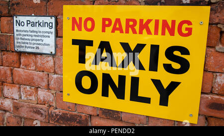 Two signs mounted on a brick wall indicating parking restrictions at Preston railway station June 2018 - Stock Image