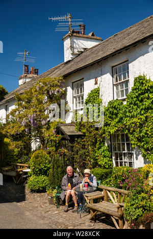 UK, Cumbria, Hawkshead, The Square, couple drinking morning coffee on outside seats beside the Honeypot store and cafe - Stock Image