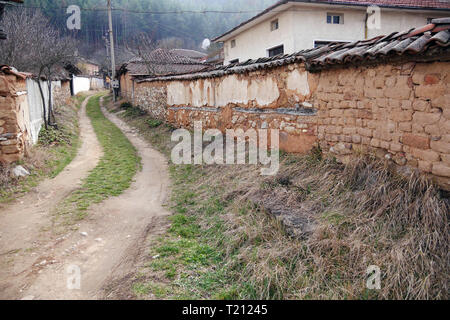 Dirt road in a semi-abandoned village. Bulgaria, Eastern Europe. People move to big cities. The villages are deserted, the houses are abandoned and cr - Stock Image