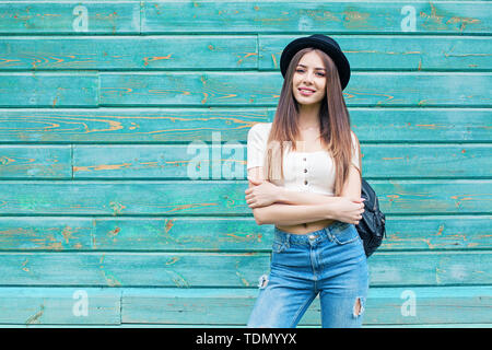 Happy young woman in blue denim on wooden background outdoors - Stock Image