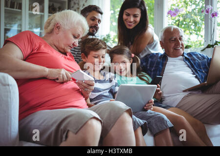 Happy multi-generation family using laptop, mobile phone and digital tablet - Stock Image