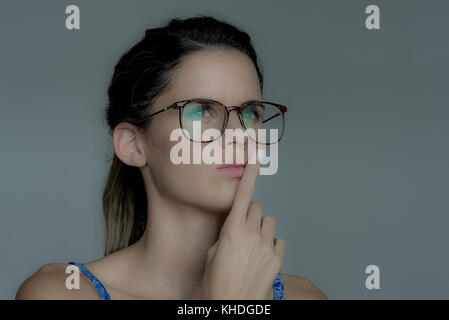 Young woman looking away in thought with finger held to lips - Stock Image