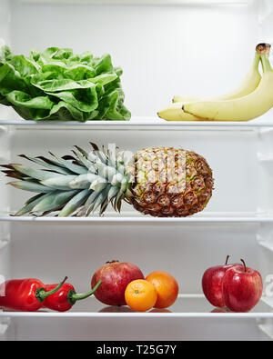 Open refrigerator containing fresh and healthy foods . Fridge filled with fruit and vegetables. - Stock Image