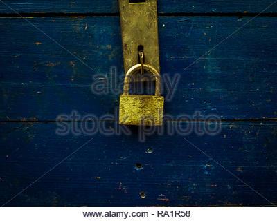 rusty gold padlock locking the blue wood box - Stock Image