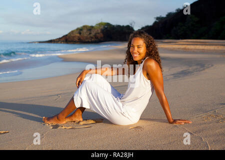 Mixed race woman relaxes on the beach in Maui, Hawaii. - Stock Image