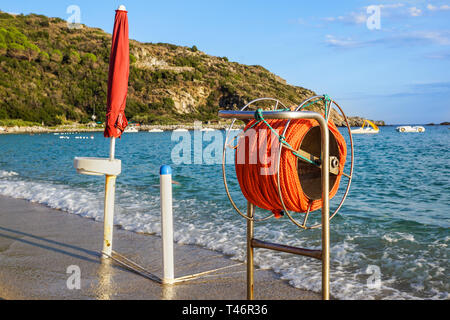 hanging orange life belt with long rope at the beach, security and safety concept . - Stock Image