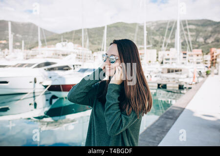 Beautiful girl talking on a cell phone on the background of yachts in the port of Porto Montenegro in Tivat in Montenegro. - Stock Image