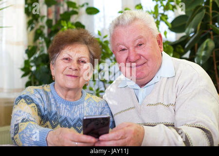 Picture of a cute senior couple taking a selfie at home - Stock Image