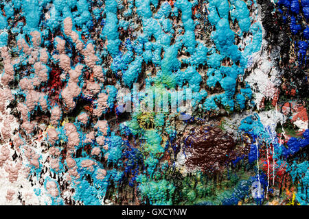 Detail of multi-coloured paint splattered wall in ship painters yard - Stock Image
