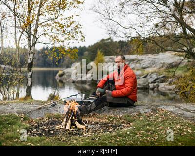 Mid-adult man sitting on lakeshore - Stock Image