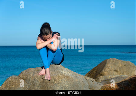 Depressed woman sitting on rocks by the sea - Stock Image