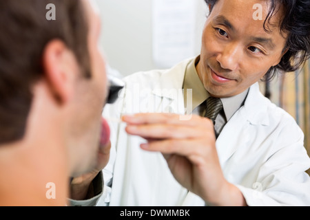 Doctor Examining Patient's Mouth In Hospital - Stock Image