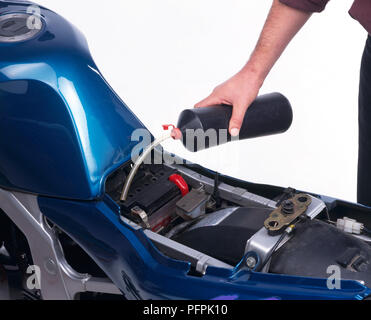 Motorcycle, battery fluid by pouring it through a tube from a plastic bottle and into the small battery openings. - Stock Image