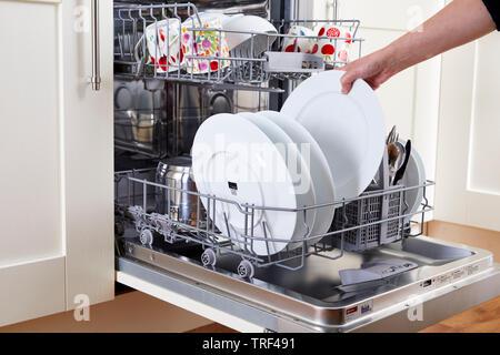 Woman unloading clean dishwasher - Stock Image