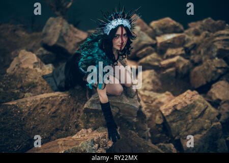 A young woman in the image of a fairy and a sorceress sitting on rock in a black dress and a crown. - Stock Image