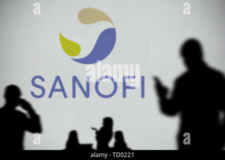 The Sanofi logo is seen on an LED screen in the background while a silhouetted person uses a smartphone in the foreground (Editorial use only) - Stock Image